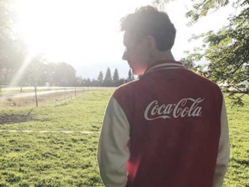 Young man wearing a Coca-Cola athletic jacket