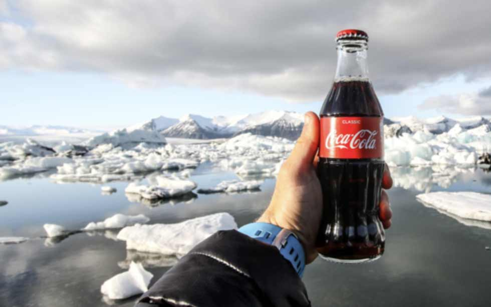 Hand holding a Coca-Cola bottle in front of a glacial lake