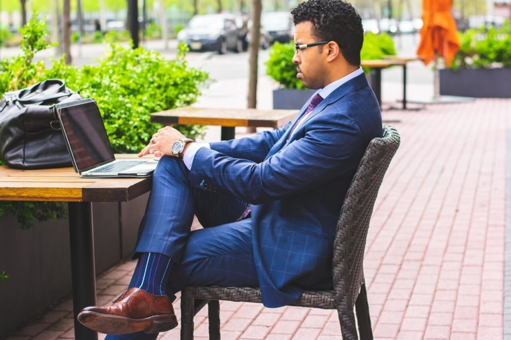 man sitting outside on laptop evaluating influencer marketing platforms